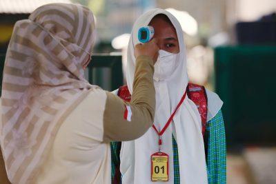 Seorang siswa sekolah dasar yang mengenakan masker diperiksa suhunya sebelum mengikuti sesi kelas, ketika sekolah dibuka kembali di tengah COVID-19 di Bekasi, di pinggiran Jakarta, 24 Maret 2021 (Foto: Reuters / Willie Kornyawan).