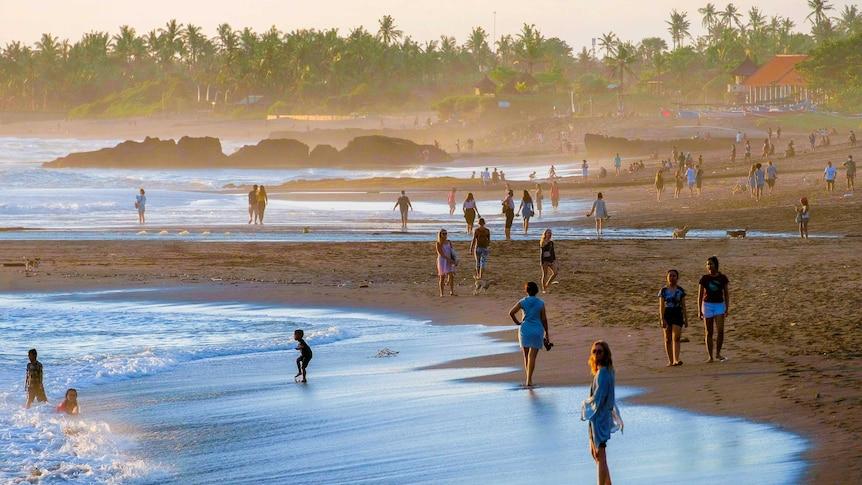 orang-orang di pantai bali dengan matahari terbenam