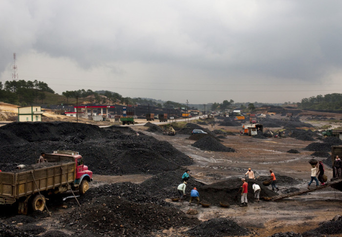 Piles of coal with workers