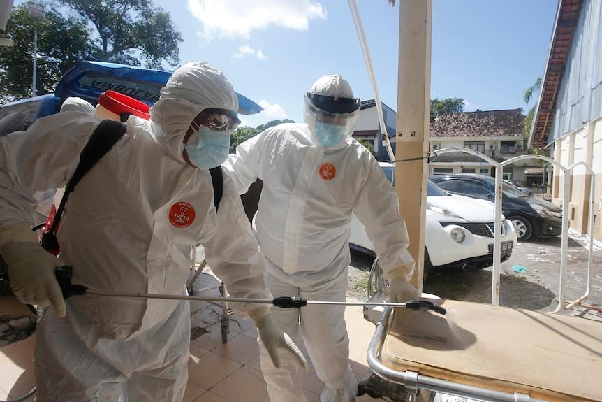 Petugas kesehatan berjas pelindung menyemprotkan disinfektan setelah membawa jenazah korban COVID-19