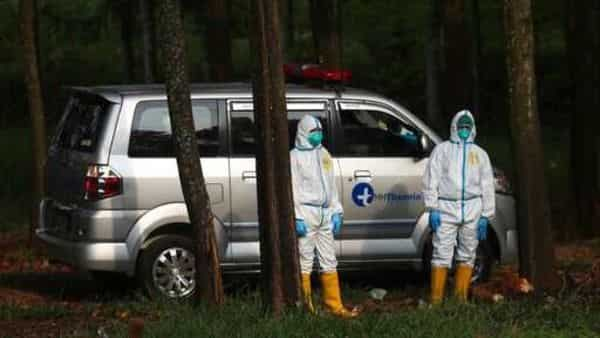 Workers in protective suits stand near an ambulance carrying the body of a COVID-19 victim as they wait for a grave to be prepared, at Cipenjo cemetery in Bogor, West Java, Indonesia. (AP)