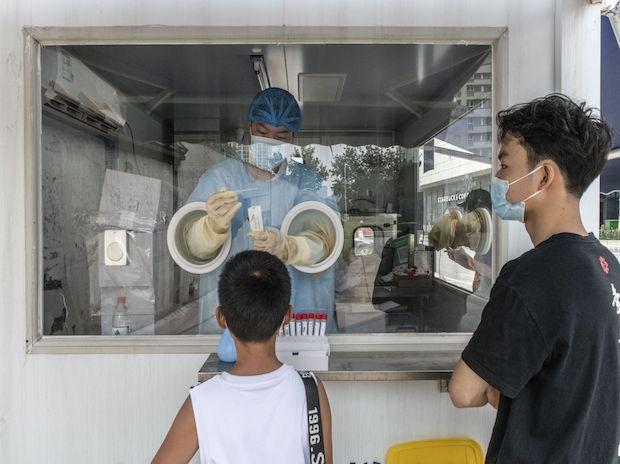 A health worker takes a swab sample at a pop-up Covid-19 testing station in the Sanlitun area of Beijing, China, on Thursday, Aug. 5, 2021. China imposed new travel and movement restrictions amid a delta-driven outbreak that's grown to over 500 sympt