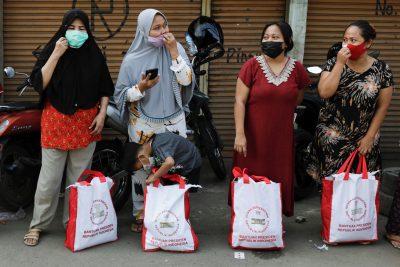 Wanita mengenakan masker pelindung, untuk mencegah penyebaran COVID-19, berdiri di jalan setelah menerima bantuan dari presiden Indonesia di Jakarta, Indonesia, 16 Juli 2021 (Foto: Reuters/Willy Kurniawan).
